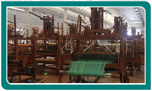Rows of wooden hand powered looms with green weaving