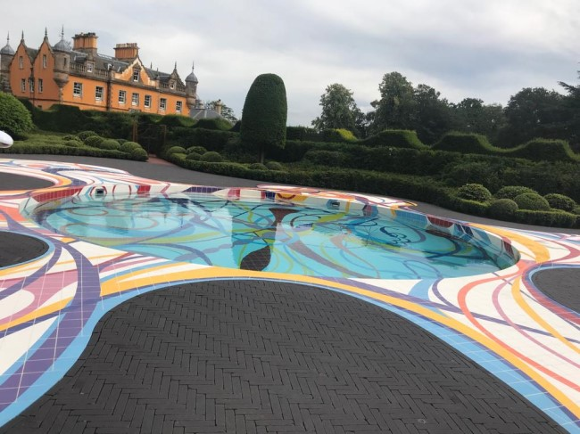 Swimming pool in grounds of big house with coloured surround on edge of pool