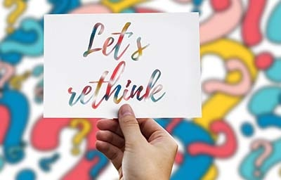 Hand holding a paper note with 'let's rethink' text with question marks in the background.
