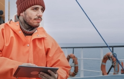 Male engineer worker with tablet in hand and offshore background.