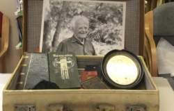 An open suitcase containing old artifacts including a black and white photograph of a man and other documents