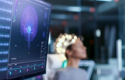Computer screen of brain scan image in foreground with person in background wearing specialist headwear