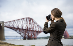 Photographer shooting landscape photo of the Forth Bridge