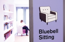 Woman sitting in chair beside graphic of chair with words Bluebell Sitting underneath