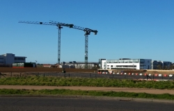 Two cranes on industrial estate with blue skies