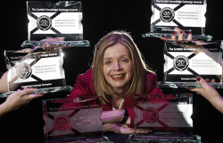Dr Siobhán Jordan surrounded by knowledge exchange awards trophies