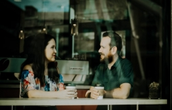 Woman and man drinking coffee together in a cafe, smiling